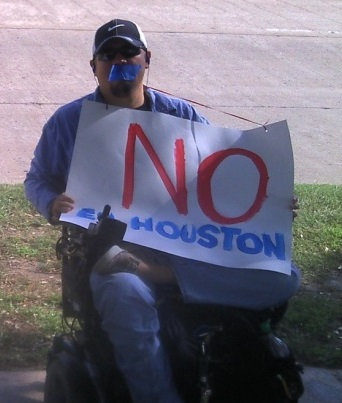 A man in a wheelchair is protesting, with tape over his mouth.