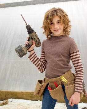 youth enjoys working on construction project, has toolbelt and drill